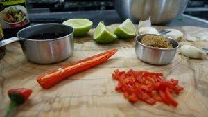 Chilipalko, viipaloitua chiliä, limelohkoja, mittakupissa kalakastiketta ja valkosipulinkynsiä. Kastikkeen valmistukseen käytettäviä ainesosia leikkuulaudalla.