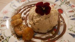 Lautasella suklaakastikepyörre, karamellisoitua banaania, mämmijäätelöä ja koristeena syötävä kukka.